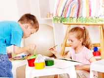 Child painting at easel. Royalty Free Stock Photography