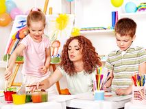Child painting at easel. Stock Photo