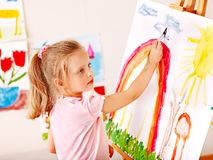 Child painting at easel. Royalty Free Stock Images