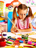 Child painting at easel. Royalty Free Stock Photo