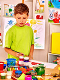 Child painting at easel Stock Image