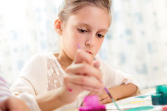 Child painting at easel in school Stock Photo