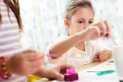 Child painting at easel in school Stock Image