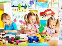 Child painting at easel. Child painting at easel in school. Teacher help Royalty Free Stock Photo
