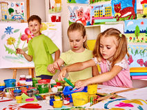 Child painting at easel. In school. Teacher help Royalty Free Stock Images