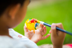 Child painting easter egg Stock Photo
