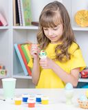Child painting Easter eggs. Beautiful girl painting eggs at home. Happy child preparing for Easter Royalty Free Stock Photography