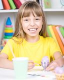 Child painting Easter eggs. Beautiful girl painting eggs at home. Happy child preparing for Easter Stock Photo