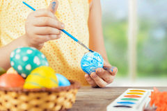 Child is painting egg for Easter. Child is painting egg in blue color for Easter holiday, face is not visible Stock Images