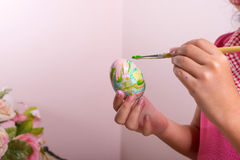 Child is painting fake egg Stock Image