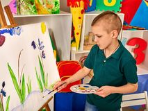 Child painting finger on easel. Kid boy learn paint school. Child painting on easel. Kid boy learn paint by brush in class school. Kindergarten interior on Royalty Free Stock Photos