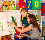 Child painting finger on easel. Kid boy learn paint school. Child painting on easel. Kid boy learn paint by brush in class school. Kindergarten interior on Royalty Free Stock Photo