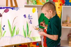 Child painting finger on easel. Kid boy learn paint school. Stock Image