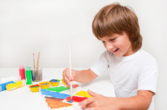 Child painting. Happy child boy painting with colors Royalty Free Stock Photos