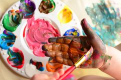 Child painting her hand with a paintbrush and mixed paint Royalty Free Stock Photos