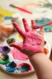 Child painting her hand with pink paint Royalty Free Stock Photography