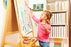 Child painting landscape picture on easel Stock Photography