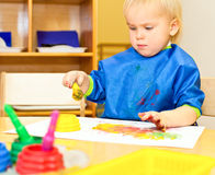 Child at painting lesson. Little girl wearing blue apron painting with watercolors stock images