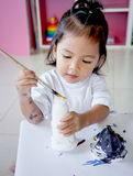 Child painting, little girl having fun to paint on stucco doll Royalty Free Stock Photo
