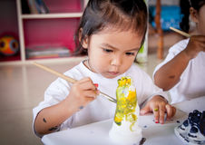 Child painting, little girl having fun to paint on stucco doll Royalty Free Stock Photography