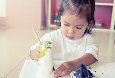 Child painting, little girl having fun to paint on stucco doll Stock Photography