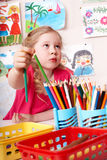 Child painting by pencil in art class. Royalty Free Stock Images