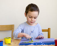Child painting picture with finger colors Royalty Free Stock Images