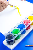 Child is painting a picture with tempera paints Royalty Free Stock Images