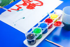 Child is painting a picture with tempera paints royalty free stock photos