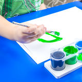 Child is painting a picture with tempera paints Stock Photography