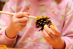 The child painting pinecone Royalty Free Stock Photography
