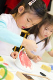 Child Painting Pottery. Children hand painting pottery royalty free stock images