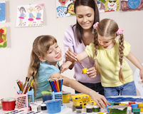 Child painting in preschool. Teacher help by little girl stock image