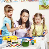 Child painting in preschool. Teacher help by little girl Royalty Free Stock Photo