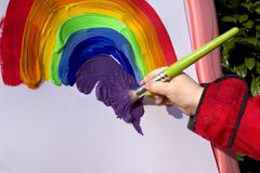 Child painting rainbow on easel in garden Stock Photo