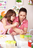 Child painting with teacher. Stock Images