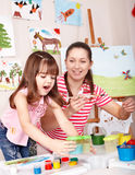 Child painting  with teacher in preschool. Royalty Free Stock Images