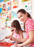 Child painting with teacher in preschool. Royalty Free Stock Image