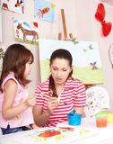 Child  painting with teacher in preschool. Royalty Free Stock Photography