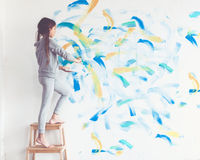 Child painting wall. 8 years old girl painting the wall at home, Instagram style toning Royalty Free Stock Images