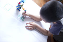 Child painting on the white paper Royalty Free Stock Photography