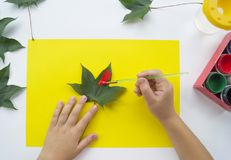 Free Child Paints A Picture Of Autumn Leaf With Paints Stock Images - 124225344