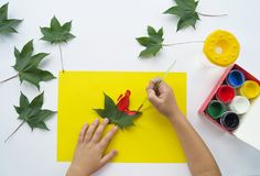 Free Child Paints A Picture Of Autumn Leaf With Paints Royalty Free Stock Photos - 124225348