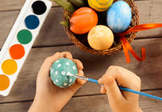 Child paints egg for Easter, focus on eggs Stock Image