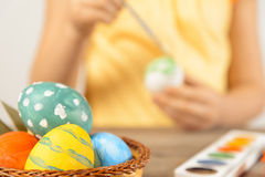 Child paints egg for Easter, focus on eggs Stock Image