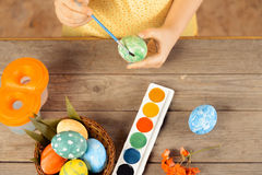Child paints egg for Easter, top view Royalty Free Stock Photo
