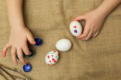 The child paints eggs for Easter stock photography