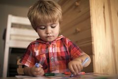 Child paints with felt-tip pens. Kid or blonde happy boy paint with felt pen. Royalty Free Stock Photography