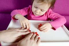 The child paints the nails of his mother with varnish stock images