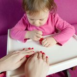 The child paints the nails of his mother with varnish royalty free stock photos